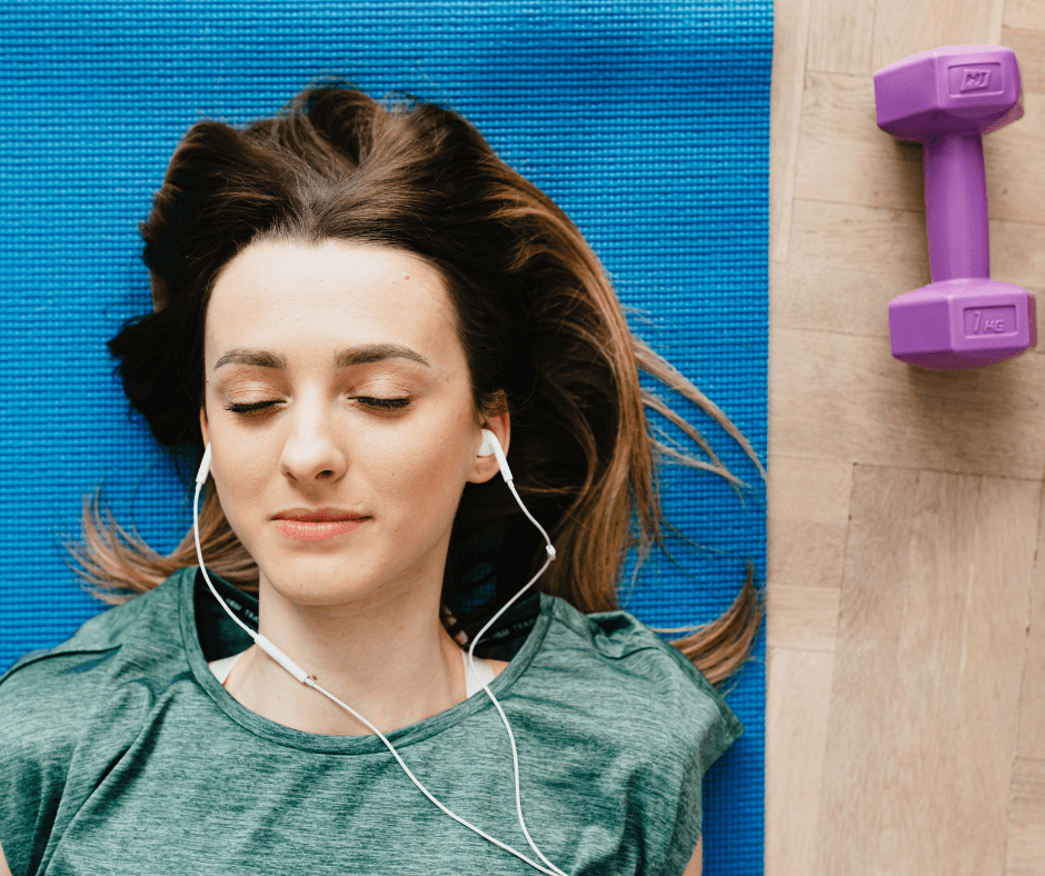 Woman lying on a yoga mat with ear phone in working out at home