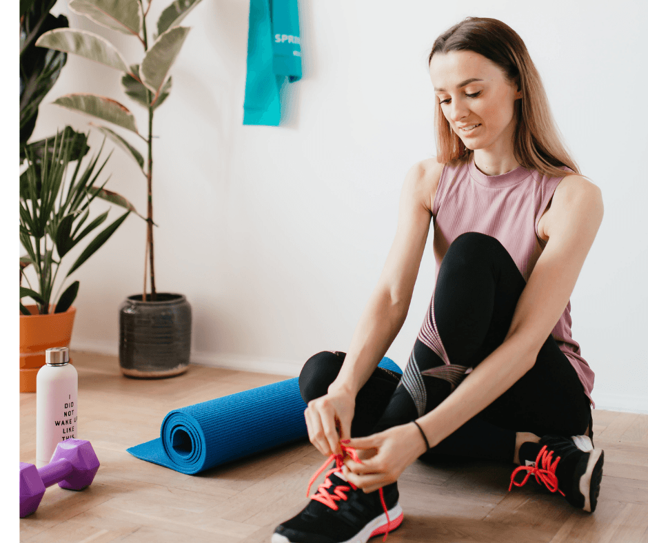 Woman sat getting ready to exercise at home tying her shoelace